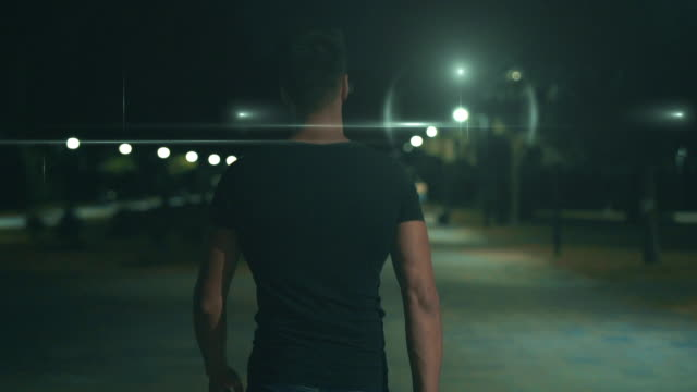 The muscular man walking in the night park. slow motion