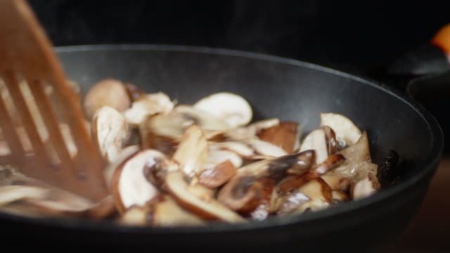 The mushrooms in the pan stir with spatula with hot steam.