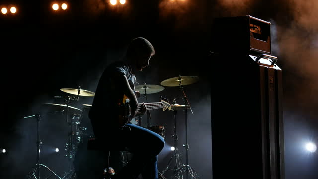 The musician connects the bass guitar before the performance on the background of yellow lights.