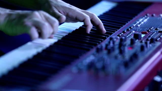 電気ピアノを弾くミュージシャン エレク トリック ピアノ、キーボード シンセサイザー ピアノの鍵盤を演じている俳優。音楽家は、コンサートのステージ上の楽器を演奏します。シンセサ� - ミュージシャン点の映像素材/bロール