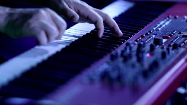 vidéos et rushes de le musicien jouant du piano électrique, piano électrique, acteur jouant sur les touches du clavier synthétiseur piano. musicien joue d'un instrument musical sur la scène de concert. synthétiseur - synthétiseur