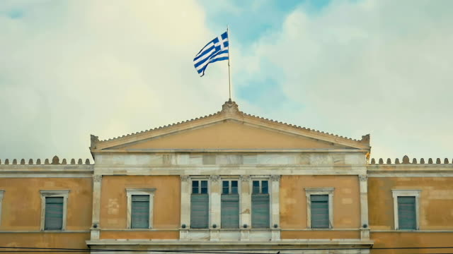 The national Greek flag is developing in the wind on the roof of the building of the Greek Parliament in Slow Motion. video