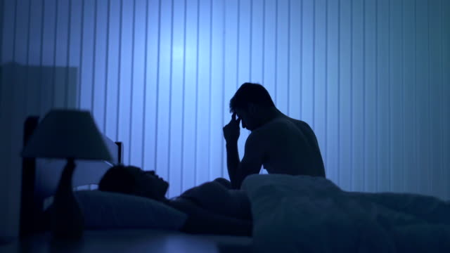 神経質になった男は、ベッドの上の女性の近くに座る。夜の時間 - 対立点の映像素材/bロール