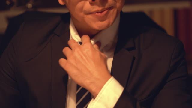 den nervösa mannen räpar krage på skjortan. asiatisk ung affärs man justera sin slips med ett seriöst tankeväckande uttryck, titta bort. - dirty money bildbanksvideor och videomaterial från bakom kulisserna