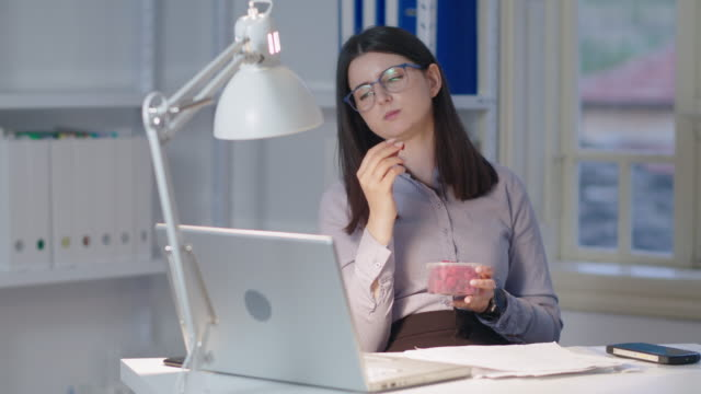 The New Normal. New office setup. Woman working alone in the new office space while COVID-19 pandemic. Taking a break with some raspberry snack.