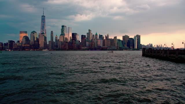stockvideo's en b-roll-footage met de nacht panoramisch uitzicht van de verlichte stad van manhattan, new york, over de hudson rivier van het liberty state park, jersey city (new jersey) - regen zon