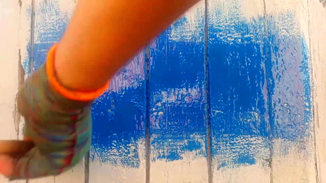 the number 2018 on the wooden board appears from under the blue paint layer video