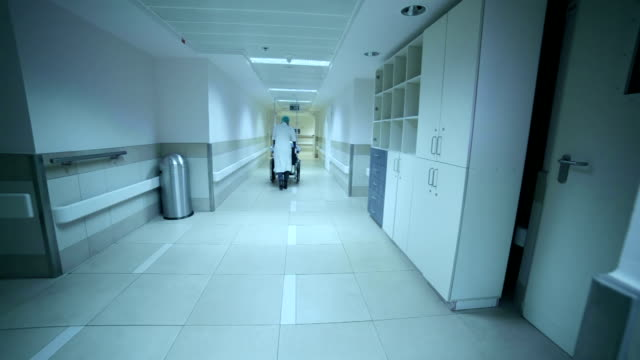 The nurse is driving a patient on wheelchair along corridor. video