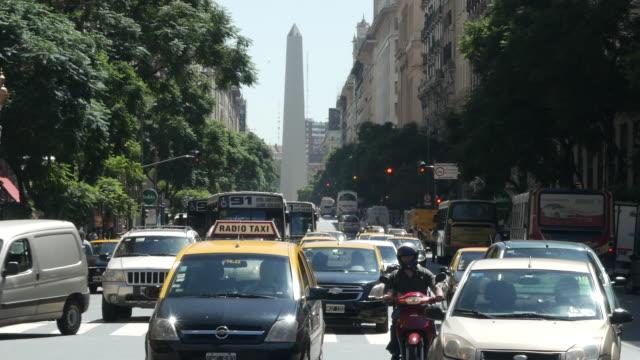 vídeos de stock e filmes b-roll de the obelisco (obelisk) national landmark & historic building street level view– 9 de julio avenue. real time. buenos aires, circa 2019 - independência