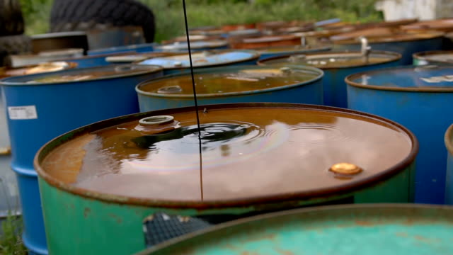 The oil is pouring on ld dirty barrels