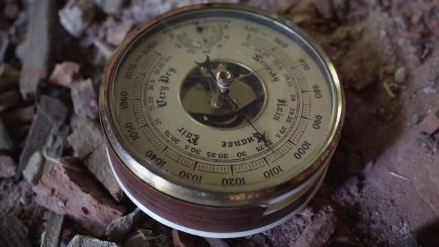 The old analogue barometer lies on the broken brick window sill.