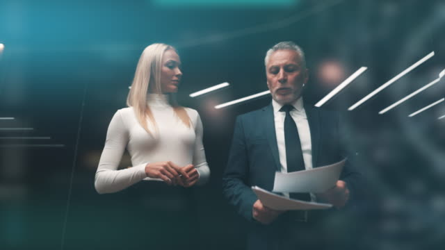 vídeos de stock e filmes b-roll de the old businessman and his beautiful business partner walking and talking. slow motion - business woman hologram