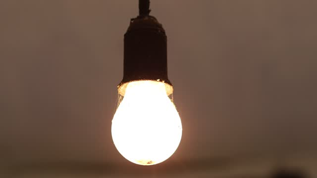 The old incandescent lamp is switched on and off