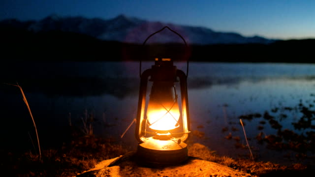 the old kerosene lantern hanging on sunrise over lake 4k - lanterna attrezzatura per illuminazione video stock e b–roll