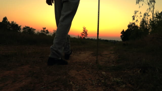 The old man using staff walking during sunset, concept healthy
