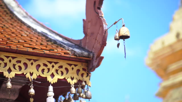 The old roof of Lanna style with mini golden bells on the roof in Doi Suthep temple against clear blue sky.