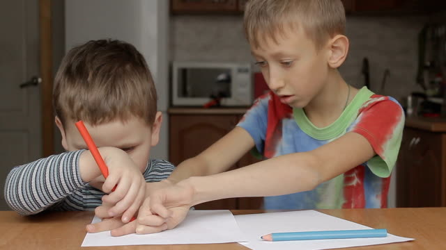 the older boy helps to draw a crayon video