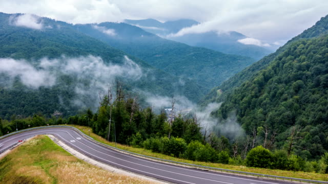 The onset of twilight in the mountains and the appearance of fog on a mountain serpentine, Evening mountain time lapse with the lights of a fast passing vehicle in the fog