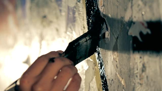 målare målar väggen i svart färg. - väggmålning bildbanksvideor och videomaterial från bakom kulisserna