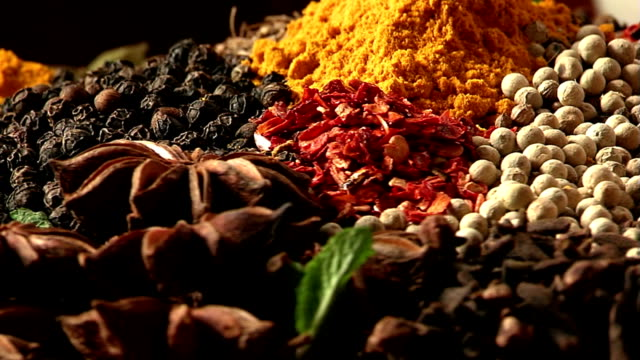The palette of different food spices. Macro. Pours black pepper peas. Mixing spices. spice stock videos & royalty-free footage