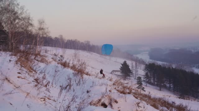 the paraplaner jumps with a running start and takes off over the snowy slope - jumping filmów i materiałów b-roll