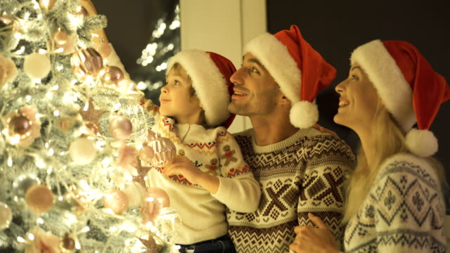 the parents with a boy decorating the christmas tree - ghirlanda decorazione video stock e b–roll