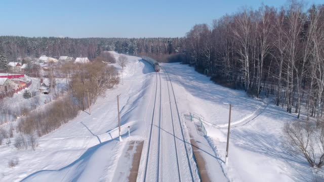 The passenger train approaching to the railroad train station The passenger train approaching to the railroad train station in the small village. The sunny winter day. 4K UHD video aerial drone footage. railroad track stock videos & royalty-free footage