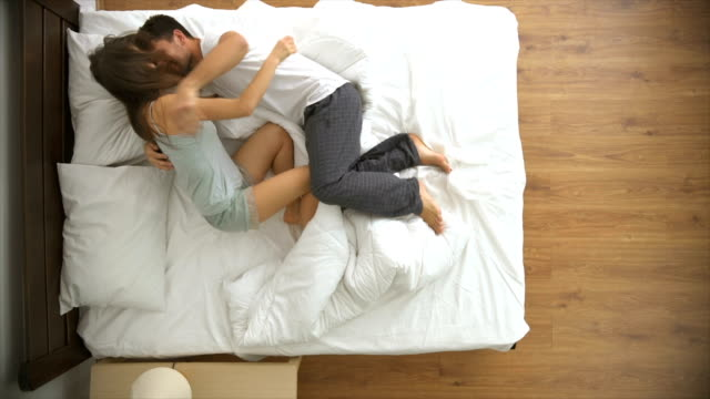 The passionate couple jumping on the bed. view from above, slow motion