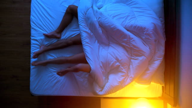 The passionate couple laying under the duvet on the bed. evening night time