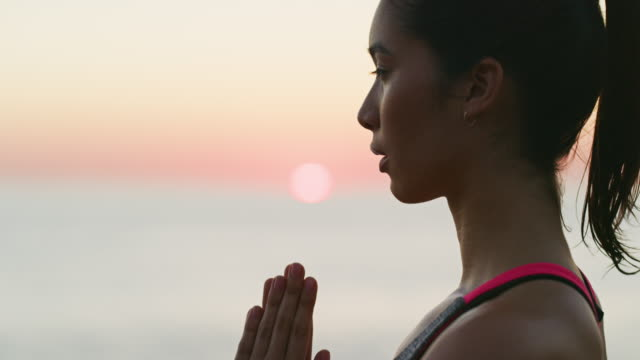 The perfect setting to do yoga 4k video footage of a beautiful young woman practicing yoga outdoors eyes closed videos stock videos & royalty-free footage