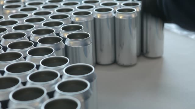 the person takes the empty aluminum cans to put them on the conveyor belt. close-up. - alluminio video stock e b–roll
