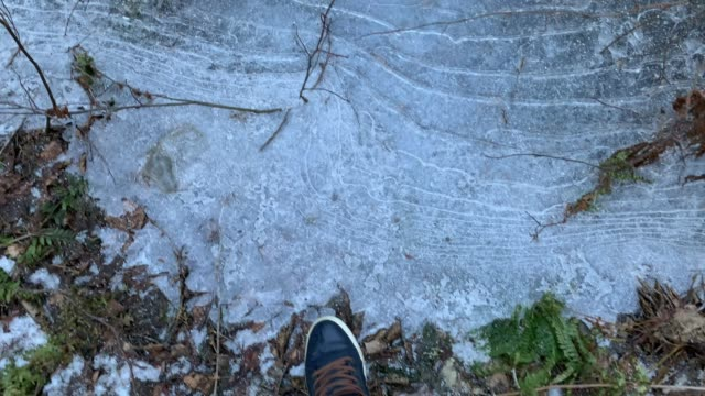 The person walks in sneakers on the frozen pools and breaks ice, jeans trousers, blue color