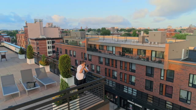 The photographer taking shots of the beautiful remote view of Manhattan on the rooftop from Brooklyn, over the residential district. video