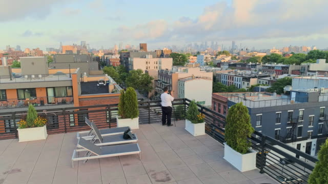 The photographer taking shots of the beautiful remote view of Manhattan on the rooftop from Brooklyn, over the residential district. Descending camera video