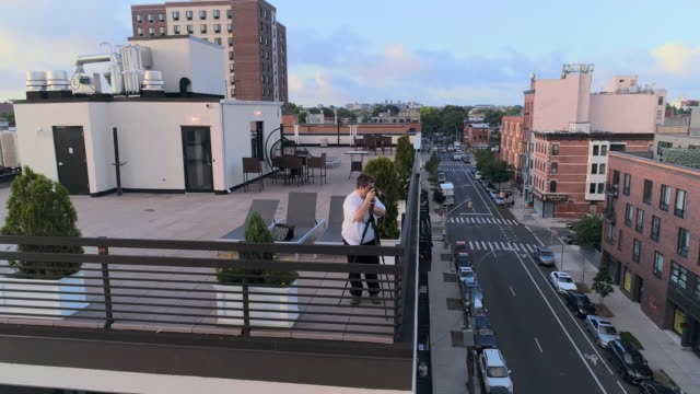 The photographer taking shots of the beautiful remote view of Manhattan on the rooftop from Brooklyn, over the residential district. Orbit camera motion. video