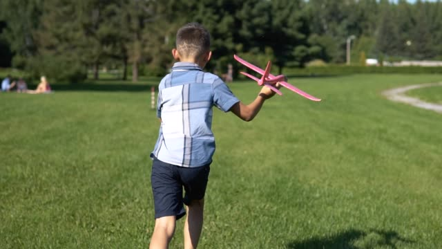 The pilot boy launches a toy plane in the park. slow motion