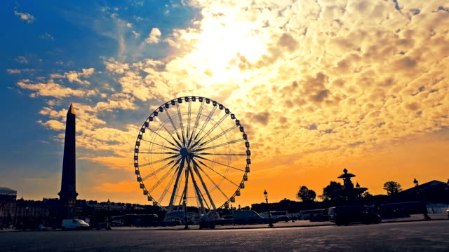 The Place de la Concorde at sunrise, largest public square in Paris, France. Big Ferris wheel and Egyptian Obelisk. Car traffic. Hyperlapse shot