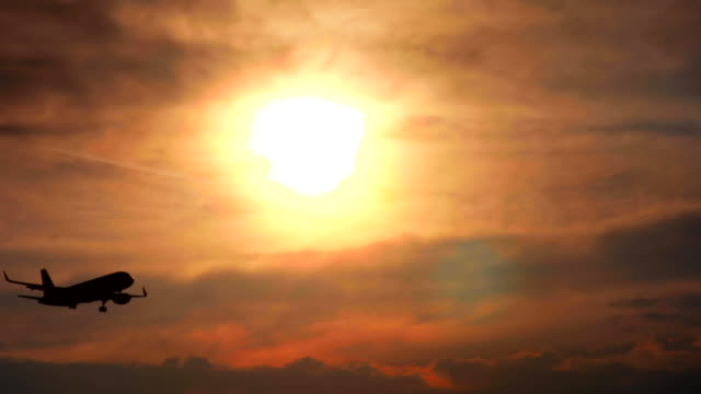The plane flies against the background of the sunset The plane flies against the background of the sunset international match stock videos & royalty-free footage