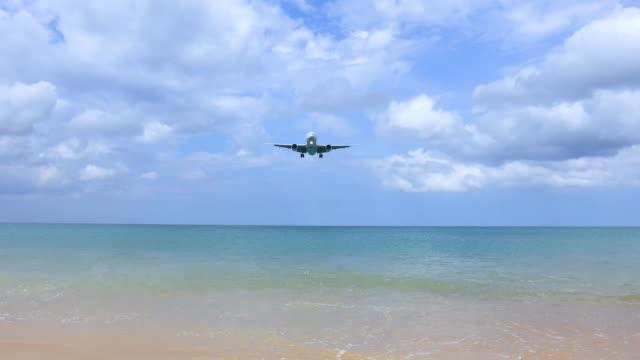 vídeos de stock e filmes b-roll de the plane is landing at phuket airport over mai khao beach in thailand. - ilha