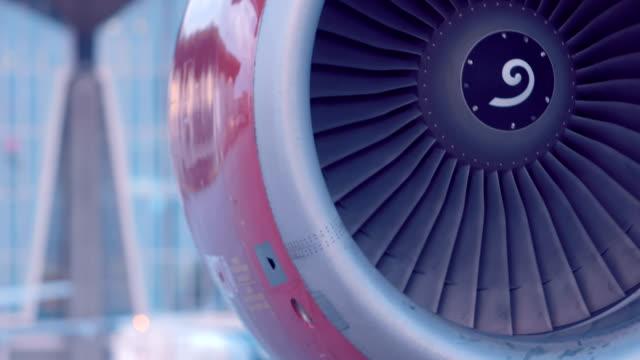 vidéos et rushes de l'avion est debout à côté du bâtiment de l'aéroport, la turbine rouge tourne - hélice pièce mécanique