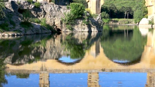 stockvideo's en b-roll-footage met de pont du gard wordt weerspiegeld in het water. - pont du gard
