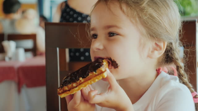 vídeos de stock e filmes b-roll de the portrait of a little girl with two pigtails, which eats a chocolate waffle, all smeared with sweets - bolo sobremesa
