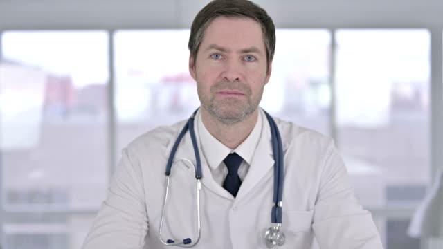 porträttet av glada medelålders läkare gör videochatt - videor med patient bildbanksvideor och videomaterial från bakom kulisserna