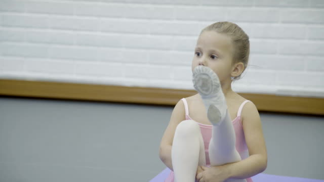The portrait of girl who sits on the mat and stretch her legs in turn during the ballet club video