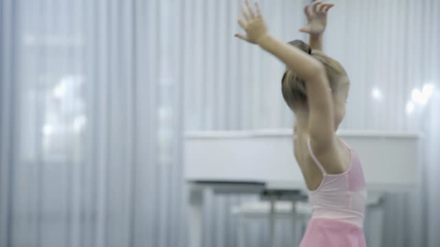 the portrait of girl with raised hands who exercises how to turn around during the ballet class - tutù video stock e b–roll