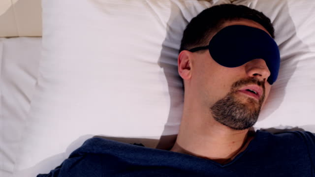 The portrait of the man in the sleep mask suffering from insomnia. 4K. video
