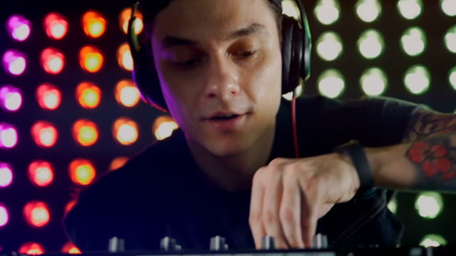 vídeos de stock, filmes e b-roll de o retrato dos sorridente dj mistura de música. close-up. hd. - dj