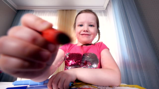 the portrait of the smiling girl drawing on camera. close-up. hd. - matita colorata video stock e b–roll