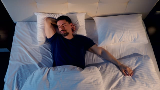 The portrait of the snoring man. Shooting from above. 4K. The portrait of the snoring man. Shooting from above. double bed stock videos & royalty-free footage
