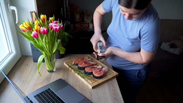 the pregnant girl is watching the show and preparing salmon with rosemary and lemon for lunch. on the table are fresh tulip flowers - filetto video stock e b–roll